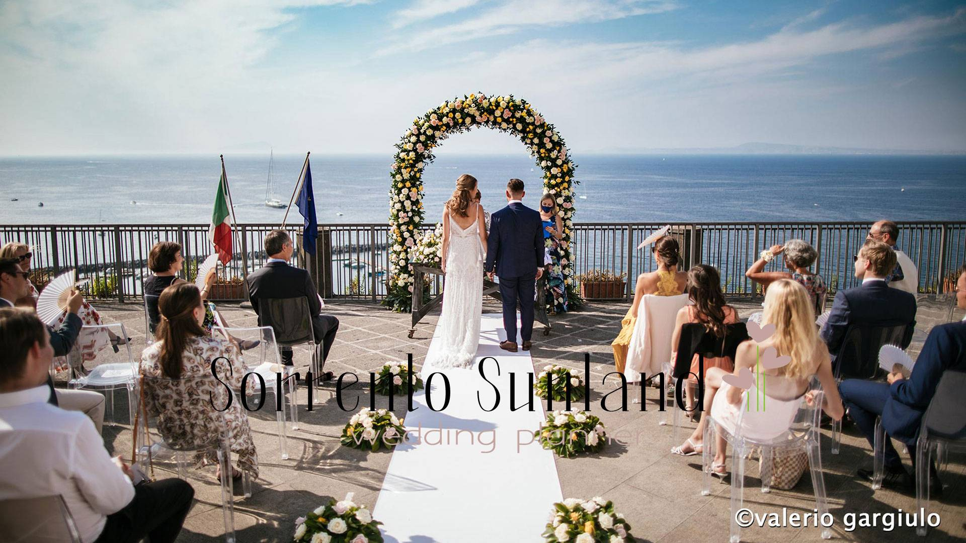 Bride and groom stand at the front of the alter with their backs turned to the guests. In front of the bride and groom stands a flower arch as well as the blue ocean and cloudy sky. Guests watch the bride and groom from their seats placed on both sides of the aisle.