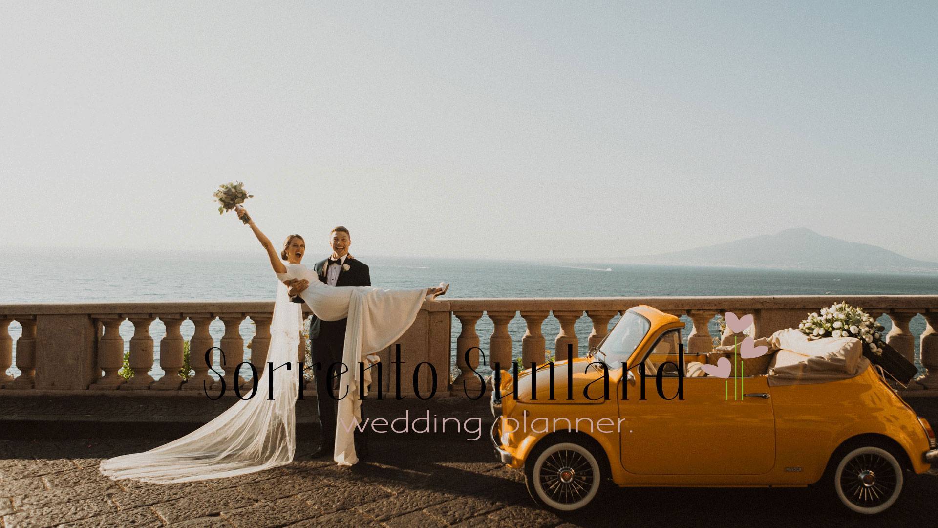 """Sorrento Town. Bride is in grooms arms facing the camera. The bride has her bouquet in hand with her armed raised celebrating their recent commitment. Her vail flows to the ground and so does the train of her white wedding dress. They stand next to a yellow vintage convertible Fiat 500 that has a flowers composition laying on it. In the background is the ocean and the lightly foggy sky, which shows an outline of a mountain. Text goes across the bottom of the image reading """"Sorrento Sunland wedding planner."""""""